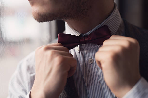 Classiness Close-up of an elegant man fixing his bow tie. bow tie stock pictures, royalty-free photos & images