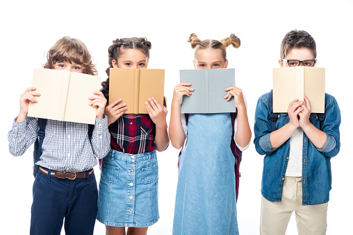 1016623732 istock photo classmates looking out from books isolated on white 1016623416