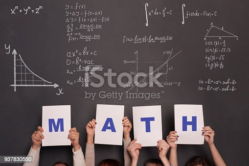 909927050 istock photo Classroom and chalkboard with formulas and numbers.Math and algebra concept. Four persons holding placards with letters MATH 937830550