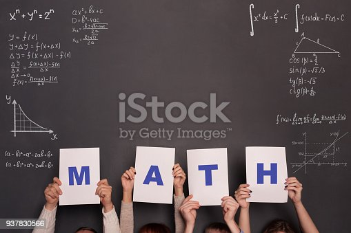 istock Classroom and chalkboard with formulas and numbers.Math and algebra concept. Four persons holding placards with letters MATH 937830566