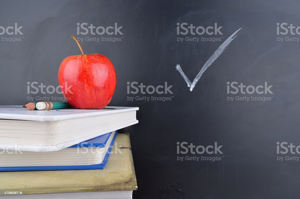 Classroom concept with books an apple and blackboard with handwriting stock photo