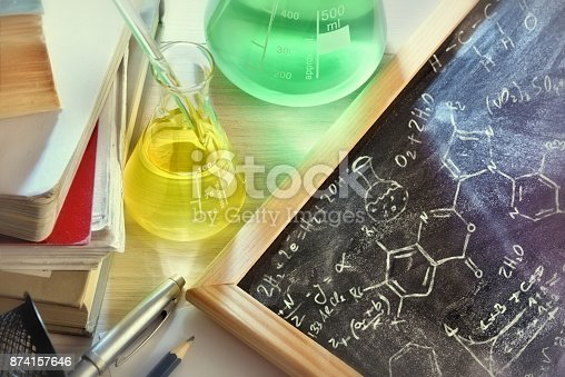 874157676 istock photo Classroom desk and drawn blackboard of chemistry teaching elevated view 874157646