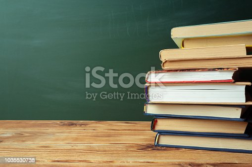 istock Classroom with blackboard, wooden table and books 1035530738