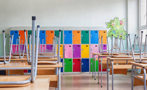 sala de aula com armários coloridos e cadeiras levantadas nas tabelas - fechado - fotografias e filmes do acervo