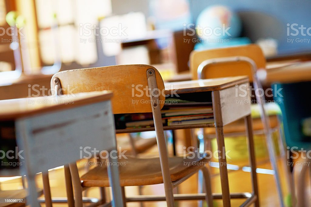 Classroom with empty wooden desks stock photo
