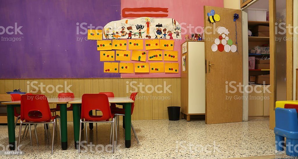 classroom with red chairs and table with drawings of children stock photo