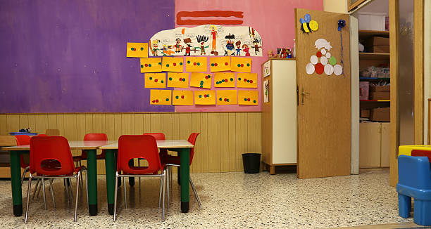 parlamentarische bestuhlung mit roten stühlen und tisch mit zeichnungen von kindern - grundschule stock-fotos und bilder
