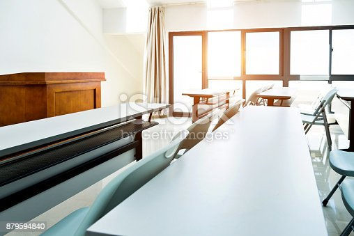 istock Classroom with tables and chairs 879594840
