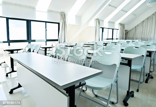 881192038istockphoto Classroom with white tables and chairs 879595174