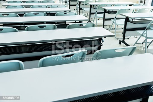 881192038istockphoto Classroom with white tables and chairs 879595226