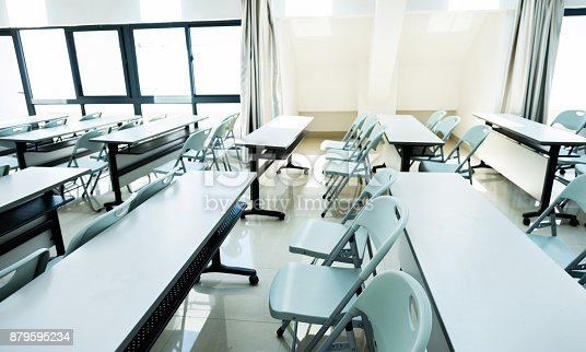 881192038istockphoto Classroom with white tables and chairs 879595234