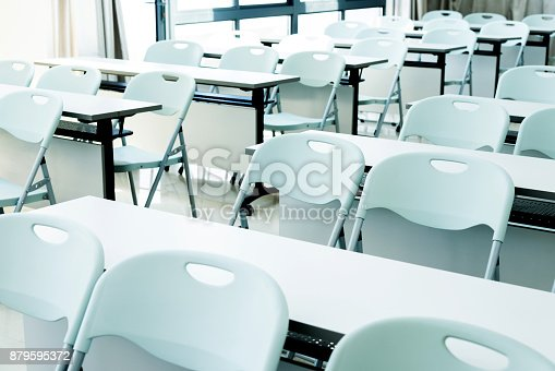 881192038istockphoto Classroom with white tables and chairs 879595372