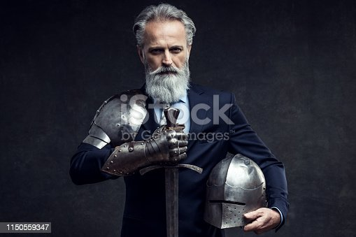 Portrait of a handsome self-confident well dressed businessman holding knight sword