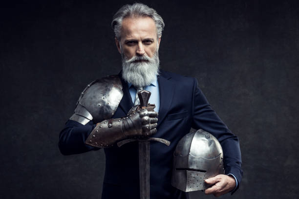 Classy dressed senior businessman with knight sword stock photo