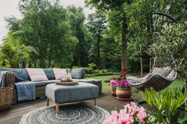Classy furniture on wooden terrace in green beautiful garden stock photo