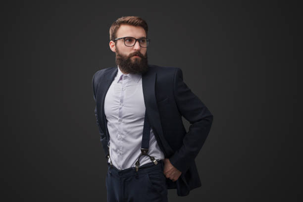 Classy gentleman in glasses Handsome elegant man with beard wearing black suit with glasses looking away on black background suspenders stock pictures, royalty-free photos & images