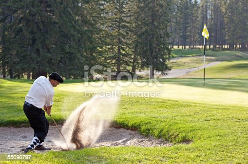 A golfer dressed in plus fours hitting a bunker shot. Horizontal image. Image taken on iconic mountain golf course in Banff, Alberta, Canada. Golfer is in his mid 30s and is wearing dressing argyle socks and classic or vintage golf apparel. There is an old-fashioned or timeless appeal in the image. Golfer is blasting out of a sand trap and is demonstrating proper technique, skill, and form on this type of short game shot.