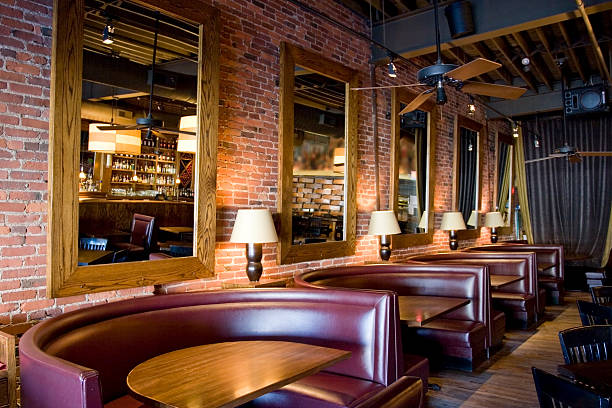 Classy Restaurant Bar with Booths, Mirrors and Red Brick Walls stock photo
