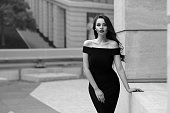 Black and white portrait of young beautiful elegant woman in black dress. Pretty sensual girl with long curly hair posing outdoors at city street