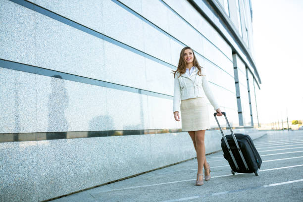 Classy young woman walking on the parking lot stock photo