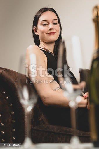 Classy young happy woman wearing a fancy dress, sitting on couch in a lounge looking at champagne glasses. Royalty free stock photo.