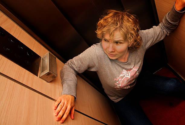 claustrophobic woman in elevator - claustrofobie stockfoto's en -beelden