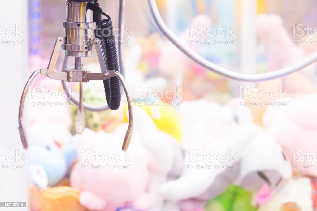 Claw Game or cabinet catches the doll.A mechanical arm selecting a random soft toy in a vending machine stock photo