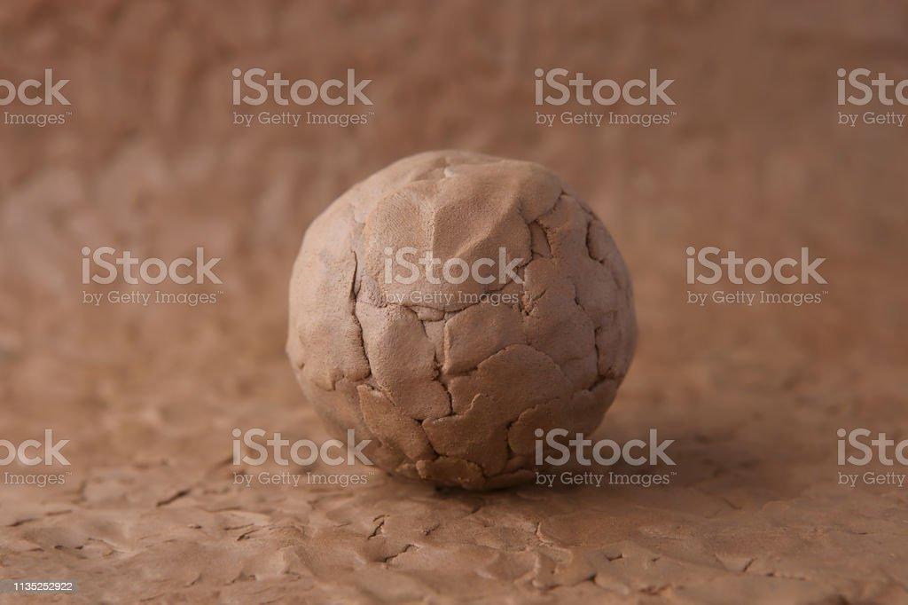 Clay ball on modeling natural clay surface. - Zbiór zdjęć royalty-free (Brązowy)