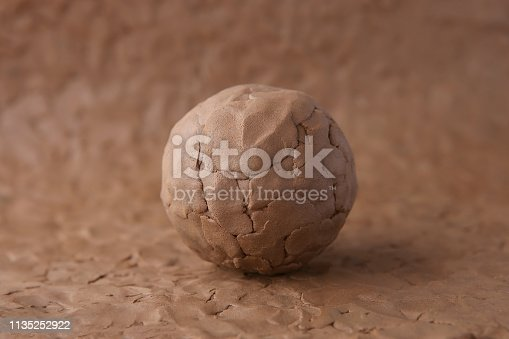 istock Clay ball on modeling natural clay surface. 1135252922