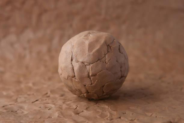 gliniana kulka na modelowaniu naturalnej powierzchni gliny. - glina zdjęcia i obrazy z banku zdjęć