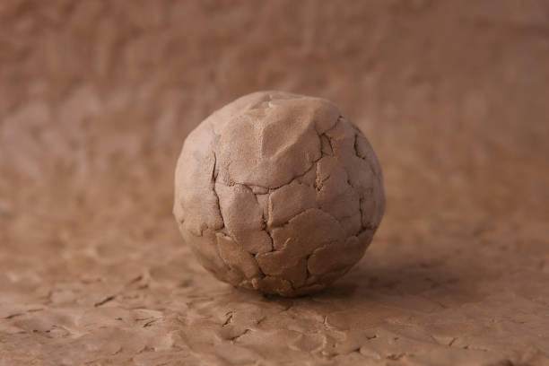 Clay ball on modeling natural clay surface. Wet clay material for craft. clay stock pictures, royalty-free photos & images