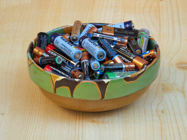 A clay bowl filled with used batteries stock photo