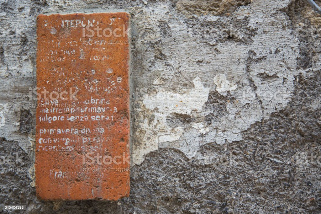 Clay bricks attached to the wall with an incomprehensible written. stock photo