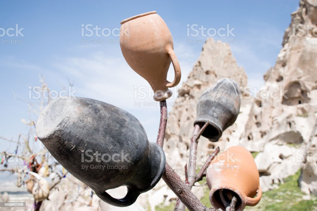Clay jugs hanging in a tree in stone monastery background, Cappadocia national park, Turkey stock photo