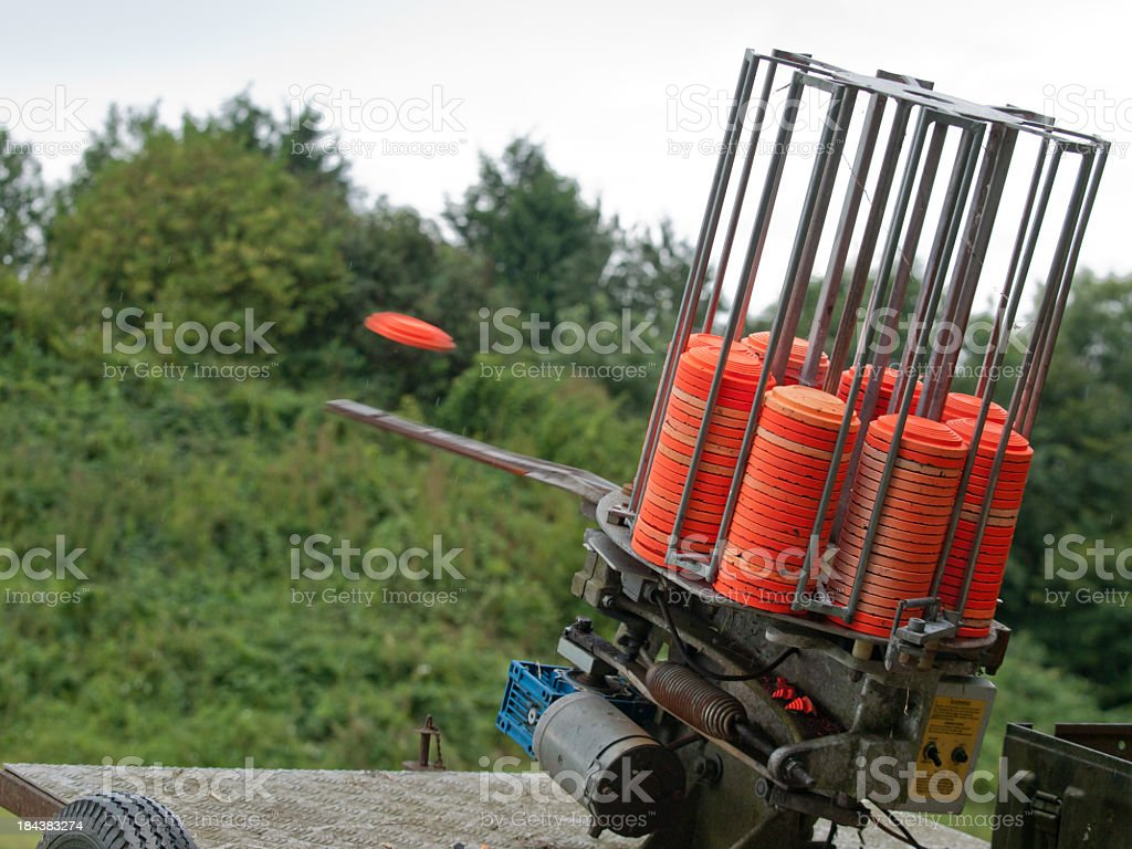 A clay pigeon is ejected out of a clay target machine stock photo
