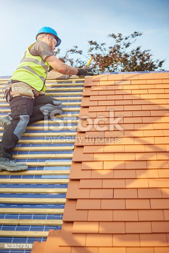 istock clay plain tiled roof being nailed 823327376