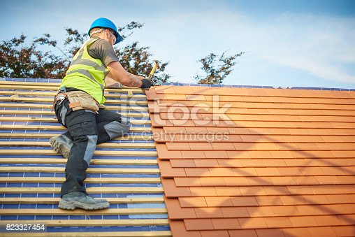 823328086istockphoto clay plain tiled roof installation 823327454