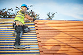 a roofer nails on the roof tiles