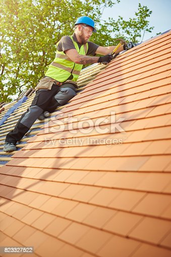 823328086istockphoto clay plain tiled roof installation 823327522