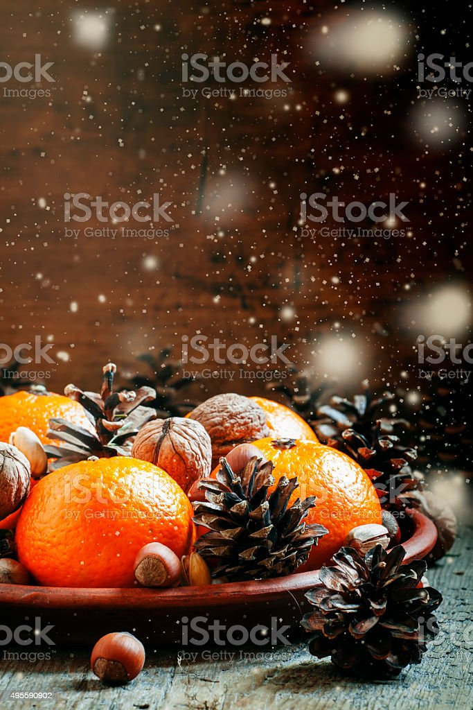 Clay plate with orange mandarins, fir cones, walnuts and other stock photo
