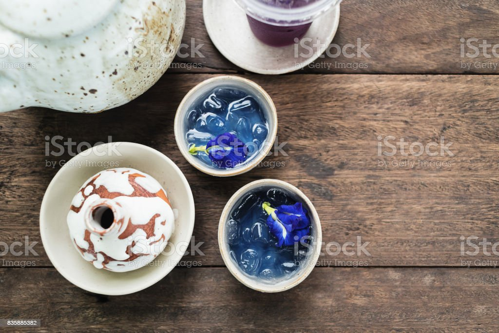 Clay pot of  iced butterfly pea tea on wooden table stock photo