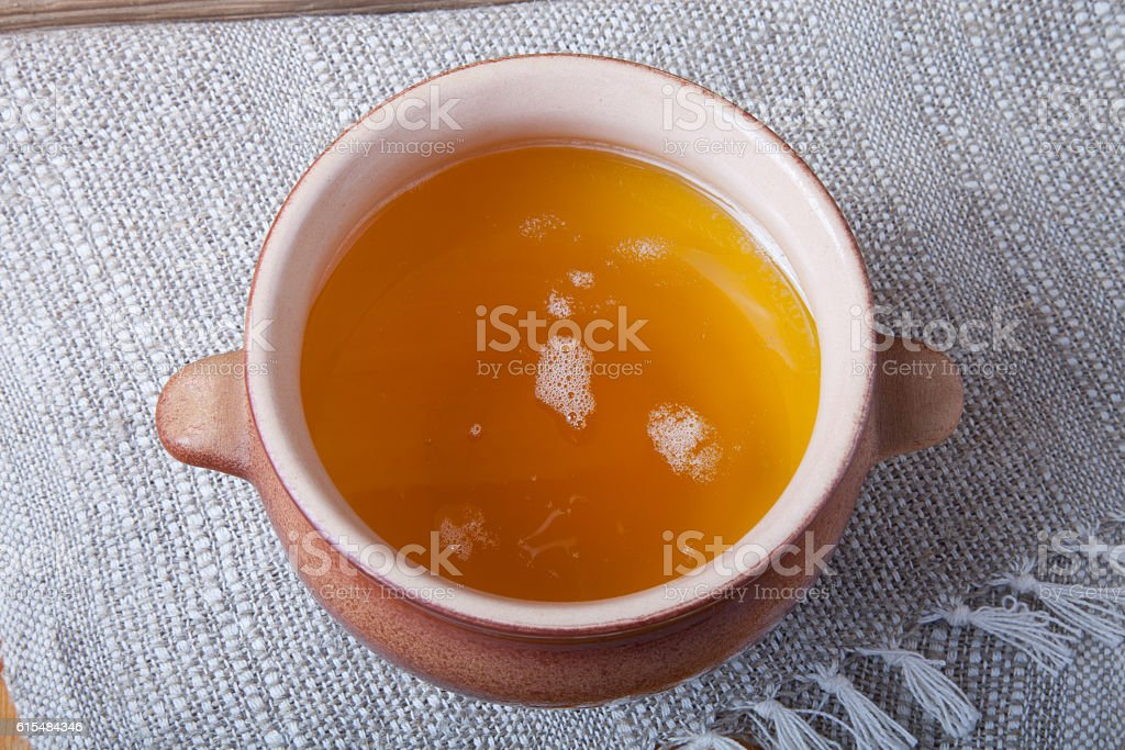 Clay pot with ghee and spoon on linen napkin stock photo