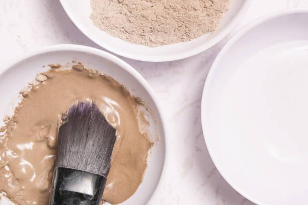 lehm-pulver und wasser - gesichtsmaske zutaten - makeup selbst gemacht stock-fotos und bilder