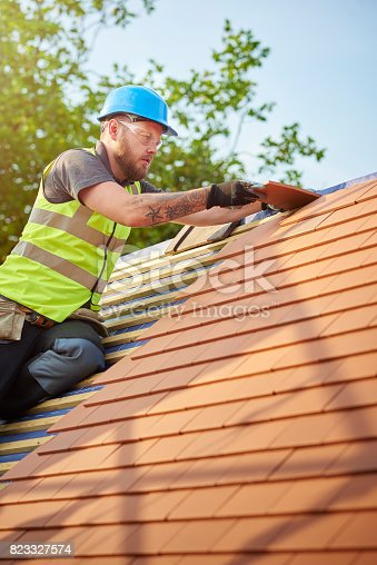 istock clay roof tile installation 823327574