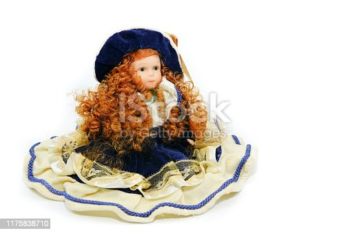 Clay statuette of a red-haired doll in a hat for a holiday on an isolated background