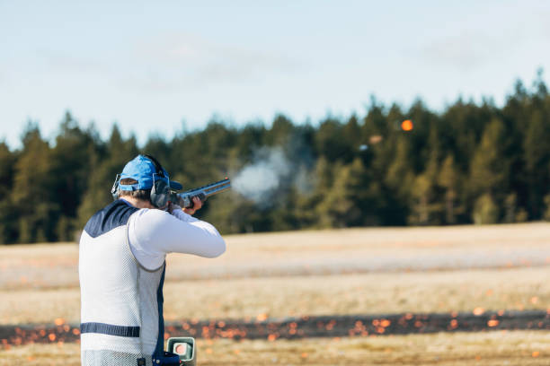 Clay target shooter Professional trap shooter shooting clay targets. shooting a weapon stock pictures, royalty-free photos & images