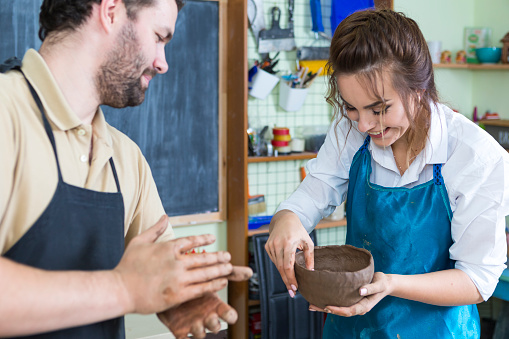 Claymaking Process Concept. Two Cheerful Professional Ceramists During a Process of Clay Preparation on Tables in Workshop. Horizontal Image Orientation