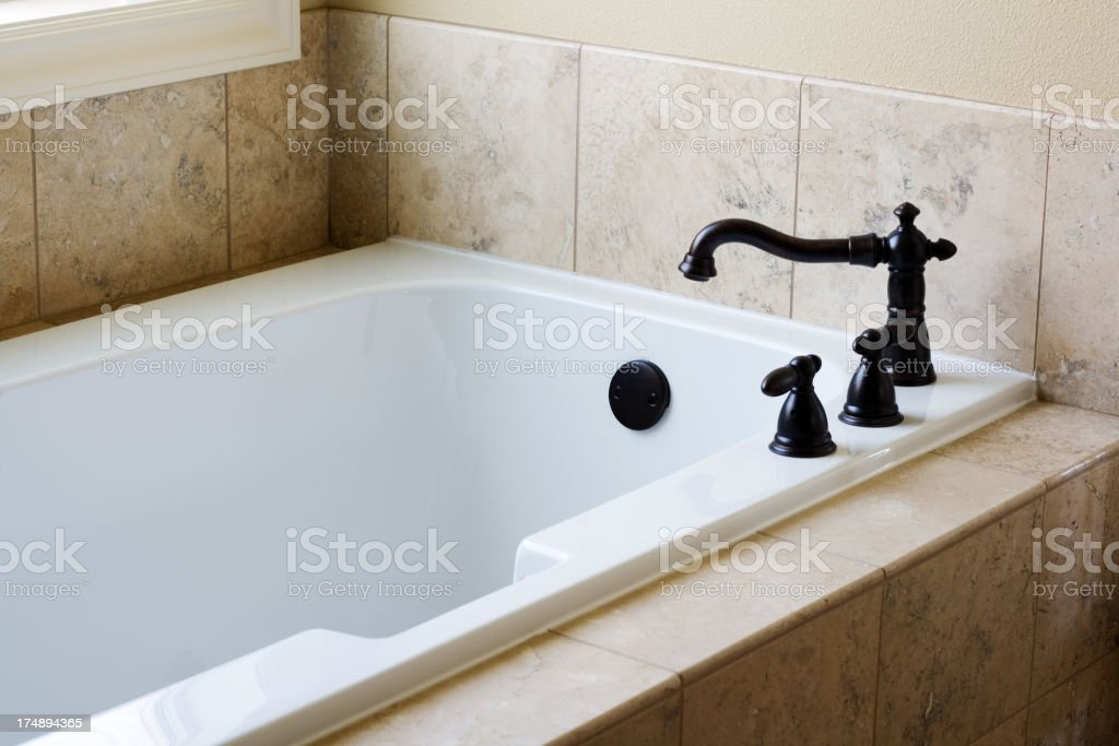 Clean and empty bathtub with cream colored tiles royalty-free stock photo