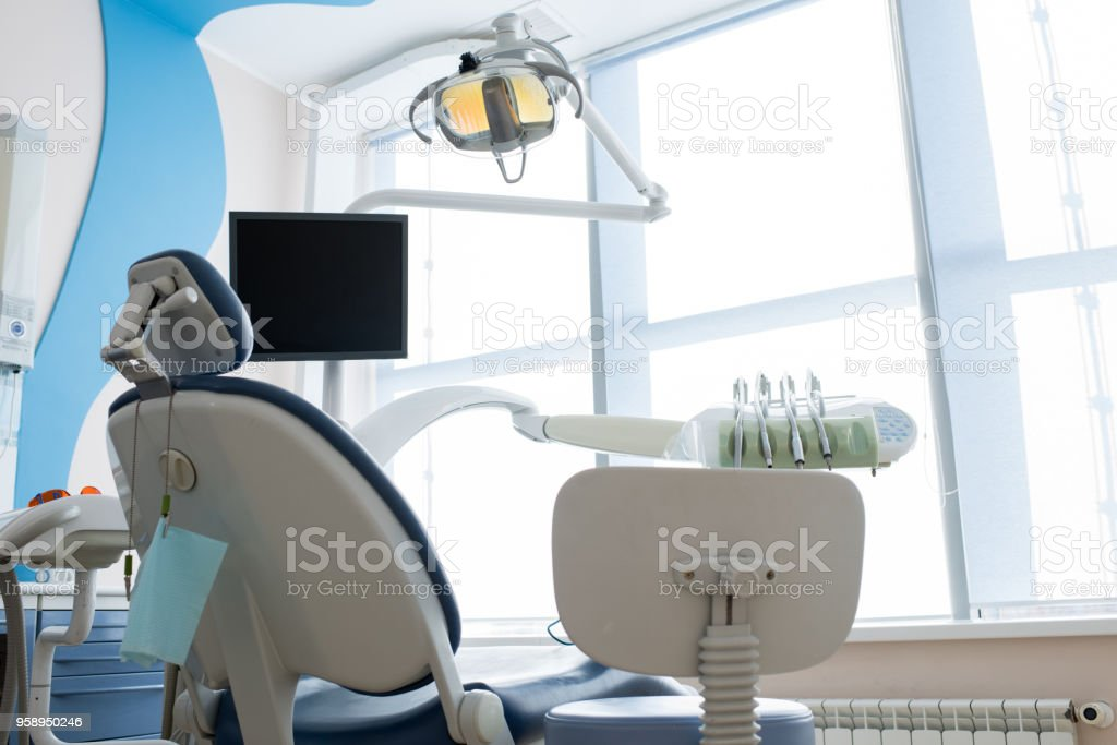 Seat and workplace of dentist in clean cabinet with big window in...