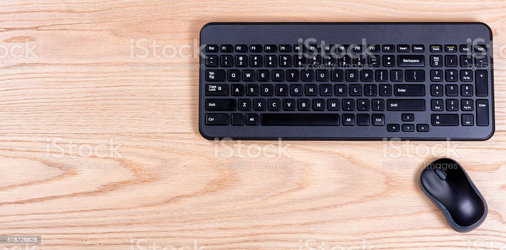 Clean and organized red oak desktop with keyboard and mouse stock photo